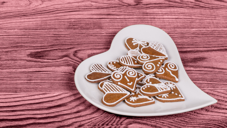 Heap of ornate hearts from gingerbread on white heart-shaped plate. Valentine's background with symbols of love and luck on pink-colored wood.