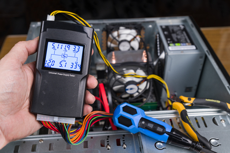 Foto de Hand tester of power supply unit. Open computer case. Professional diagnostic device. Digital measuring tool, connectors, colorful cables, pliers and screwdriver. PC hardware maintenance. Technician. - Imagen libre de derechos
