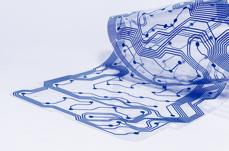 Foto de Electronic flex circuit board. Clear membrane of dismantled computer keyboard. Silicone sheet. PCB detail curled to a roll. Artistic design. Abstract bent plastic film. Blue pattern. White background. - Imagen libre de derechos