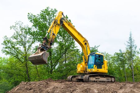 Photo for Yellow belt excavator on construction site. Hydraulic earth mover. Backhoe loader. Rotating operator cabin, shovel and continuous tracks. Pile of soil, spring sky, green tree tops. Building industry. - Royalty Free Image