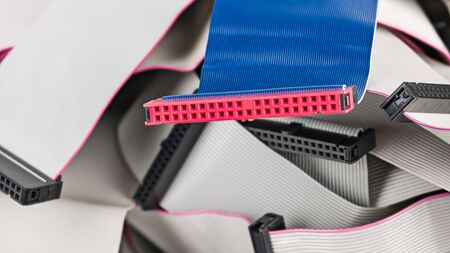 Photo pour Blue parallel multi wire ribbon cable with pink connector on pile of white flat cords. Detail of internal bus attachment. Integrated drive electronics for connection of different data storage devices. - image libre de droit