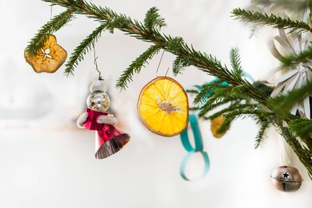 Photo pour Close-up of decorated retro Christmas tree on white background. Spruce branch detail with hanging Xmas decorations as orange or apple slice, red figurine, metal jingle bell and paper chain or flower. - image libre de droit