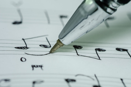 Closeup photo of hand writing music note with ballpoint pen