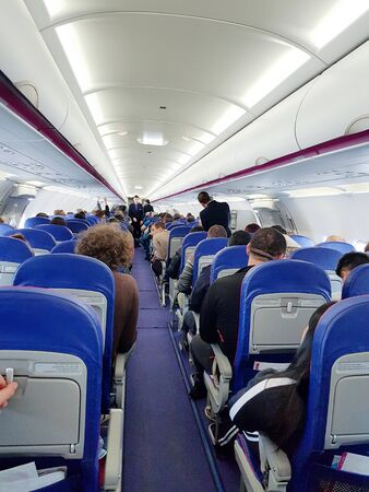 Photo pour Interior of an airplane with passengers on seats waiting to take off. - image libre de droit