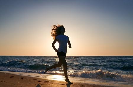 Photo pour beauty woman run on sea beach on sunset - image libre de droit