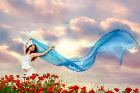 Photo pour beauty woman in poppy field with blue tissue under sky - image libre de droit