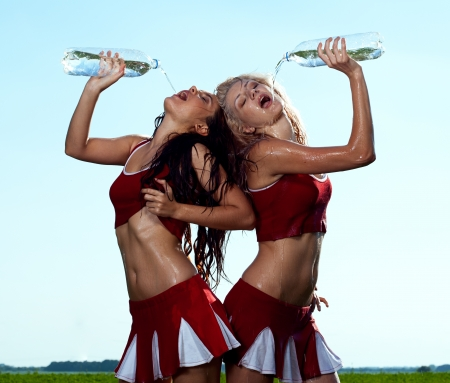 beauty cheerleader with water on field under blue sky