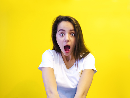 Amazing teenager opened his mouth and screamed with an amazed face. Studio shot, yellow background