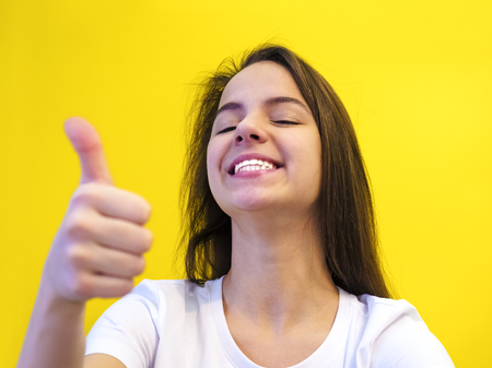 Enthusiastic motivated attractive young woman giving a thumbs up gesture of approval and success with a beaming smile