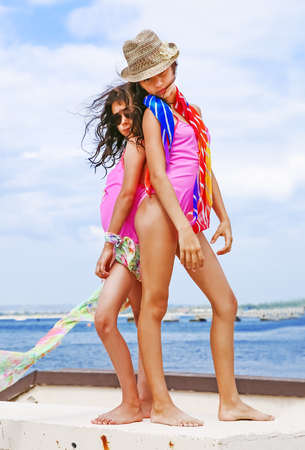 Two model young friends in a swimsuit are standing on a stone pier. Against the background of the water and the blue sea. Entertainment, recreation, travel, adventure - concept