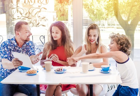 Happy family eating breakfast and using tablet. A big company with a digital tablet in cafe, smiling happy man and his three children looking to the screen, using internet, buy online