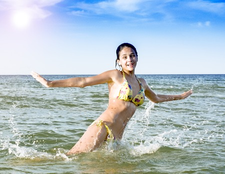 Foto de A girl jumping and immersed in a refreshing sea, ocean, on a hot summer day - Imagen libre de derechos