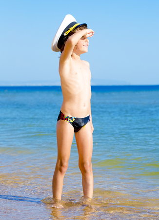 Foto de Funny child in black swimming trunks in a sea cap looking into the distance on the background of blue sea and sky - Imagen libre de derechos