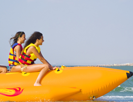 Photo pour extreme speed attraction in the sea.ea attraction. Group of young enjoying a ride on a banana boat on sunny summer day. Beach water sport - image libre de droit