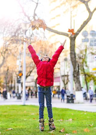 Foto de Happy child throwing leaves in autumn park - Imagen libre de derechos