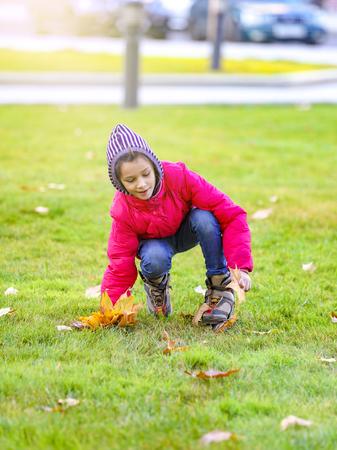 Foto de happy little child, sweet girl smiling and collecting yellow leaves in the autumn city park walk outdoors - Imagen libre de derechos