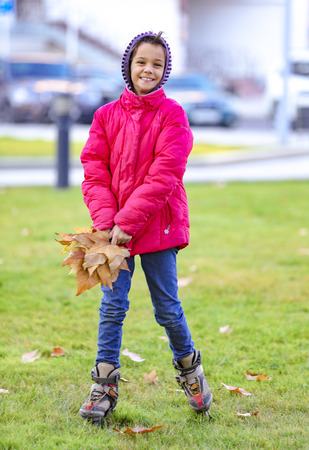 Foto de happy little child, sweet girl laughing and holding yellow leaves in the autumn city park walk outdoors - Imagen libre de derechos