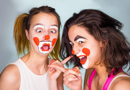 Photo pour Ridicule, taunt concept. Two friends pointing fingers at each other and smiling. Studio shot, gray background. Family in funny disguise on color background. April fools day celebration - image libre de droit