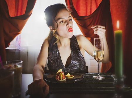 Photo pour A beautiful drunk girl in a restaurant eating dessert. Stunning girl are sitting in a cafe and drinking champagne.Vintage style. Selective focus.Gluttony concept. - image libre de droit