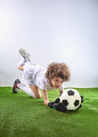 Photo pour Goalkeeper lying on the grass catches a ball. Excited little toddler boy playing football on soccer field against light background. Active childhood and sports passion concept. Save space - image libre de droit
