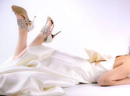 Photo pour Womens feet in white shoes. Bride lying on the floor. Copy space - image libre de droit