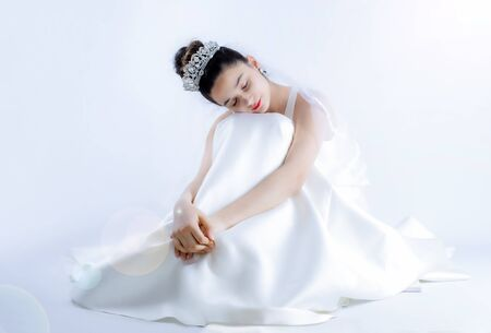 Photo pour A bride sitting on the floor with her eyes closed. Happiness and fulfillment of dreams concept. Copy space - image libre de droit