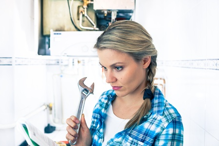 Beautiful Girl Is Learning How to Repair a Boiler Using a Pipe Wrench
