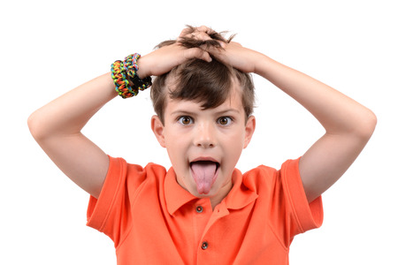 young boy with hands in hair and tongue sticking out isolated white background