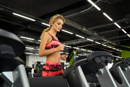 Beautiful young sporty woman running on treadmill in gym. Pretty woman working out indoors at fitness studio.Fitness. Healthy lifestyle.