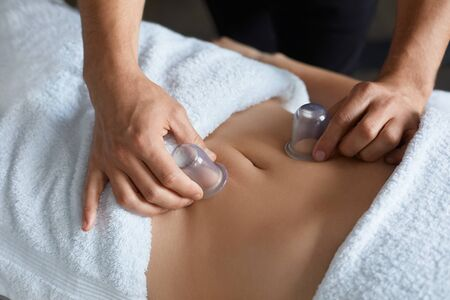 Photo pour Young beautiful woman enjoying cupping massage in spa.Professional massage therapist is treating a female patient in apartment.Relaxation,beauty,body and face treatment concept.Home massage. - image libre de droit
