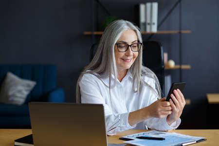 Photo for Senior grey-haired beautiful woman using smartphone and smiling. Happy businesswoman using mobile phone apps, texting message, browsing internet, shopping online. Mature people with mobile devices. - Royalty Free Image