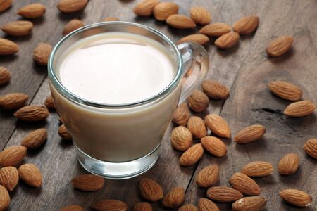 Photo for Almond milk in a glass cup on a wooden table. almonds and milk. - Royalty Free Image