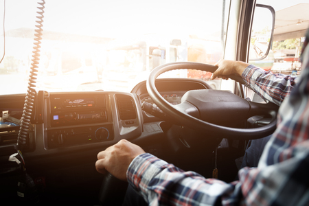Photo pour Truck driver keeps driving with one hands and change gears,The man Behind Semi Truck Steering Wheel,spot focus. - image libre de droit