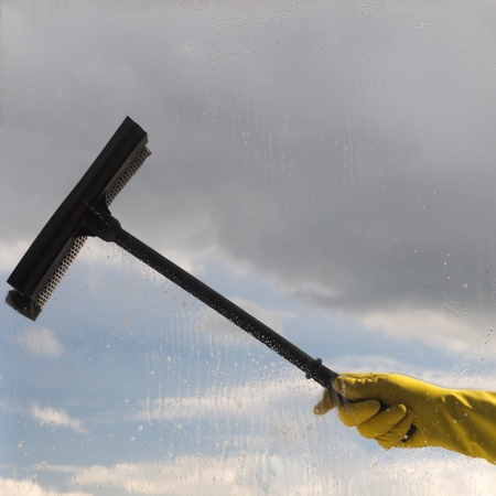 Hand in yellow protective glove washing and cleaning window with professionally squeegee on background of cloudy sky. windows cleaning. Maid cleans window.