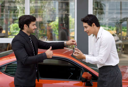 Photo pour A Persian businessman in a black suit smiles and thumbs up while handling sport car key to the valet service staff. - image libre de droit