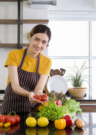 Photo for Young asian housewife holding red tomatoes with both hands. The Basket full of various kinds of vegetables. Morning atmosphere in a modern kitchen. - Royalty Free Image