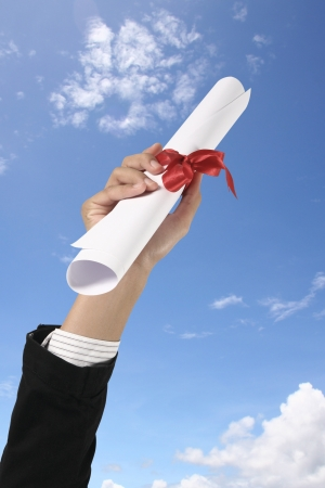 Diploma with a red ribbon in hand on sky