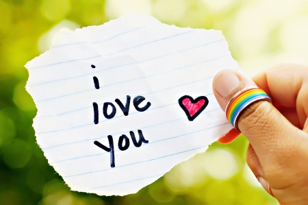 Photo pour Hand with rainbow ring holding paper that says I love you  - image libre de droit