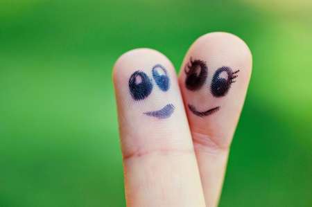 Two finger puppets smiling at one another