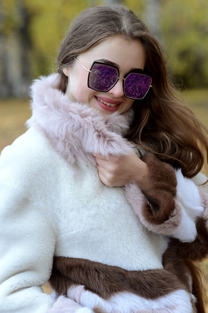 Photo for girl in a coat and sunglasses walking in the woods - Royalty Free Image