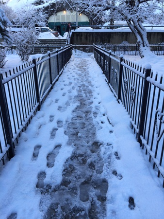 Snowy icy footprints leading to entrance to NYC subway