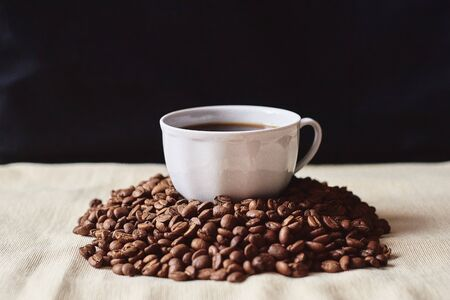 Photo pour A Cup of espresso coffee drink on a handful of roasted brown coffee beans - image libre de droit