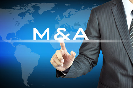 Businessman hand touching M   A on virtual screen - merger   acquisition concept