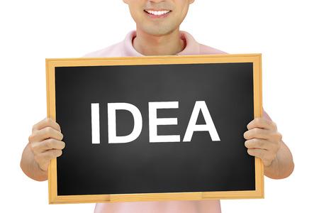IDEA word  on blackboard held by smiling man