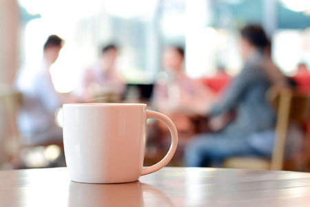 Photo pour Coffee cup on the table with people in coffee shop as blur background - image libre de droit