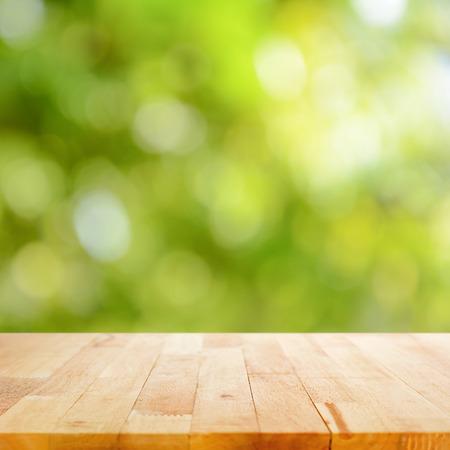 Photo pour Wood table top on green bokeh (or lens flare) background - image libre de droit