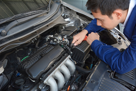 Auto mechanic (or technician) fixing car engine