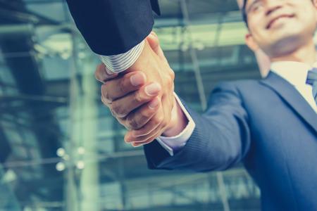 Handshake of businessmen in vintage (retro) color effect - success, congratulation, greeting & business partner concepts