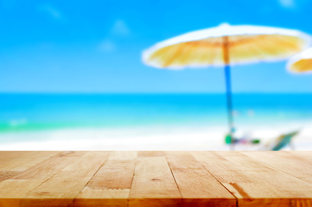 Wood table top on blurred blue sea and white sand beach background - can be used for display or montage your products