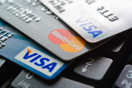 Photo pour Group of credit cards on computer keyboard with VISA and MasterCard brand logos - image libre de droit